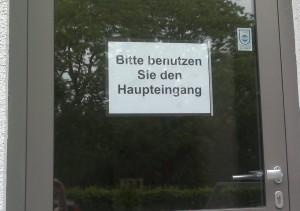 Schild mit dem Text: Bitte benutzen Sie den Haupteingang